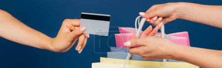 cropped view of women holding shopping bags and credit card isolated on blue