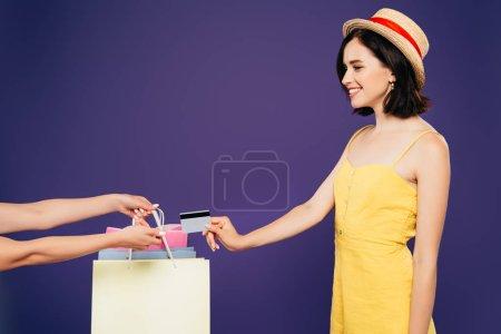 Photo pour Fille souriante dans un chapeau de paille prenant des sacs à provisions et donnant carte de crédit isolé sur violet - image libre de droit