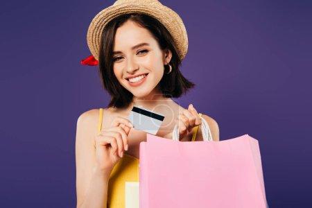 Photo pour Fille souriante en chapeau de paille avec sacs à provisions et carte de crédit isolé sur violet - image libre de droit