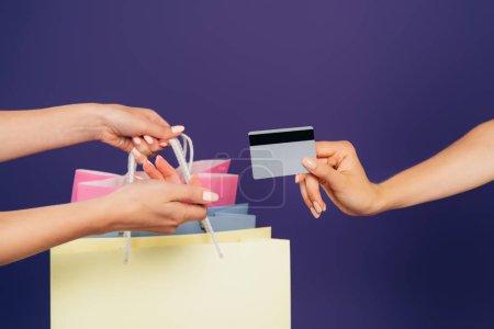Photo pour Vue recadrée des femmes tenant des sacs à provisions et carte de crédit isolé sur violet - image libre de droit