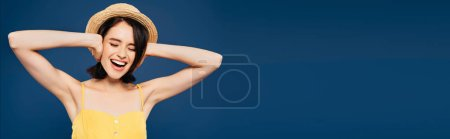 Photo for Panoramic shot of girl in straw hat with hands on ears screaming isolated on blue - Royalty Free Image