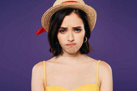 triste fille en paille chapeau regarder caméra isolé sur violet