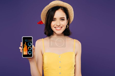 Photo for Smiling girl in straw hat holding smartphone with business app isolated on purple - Royalty Free Image