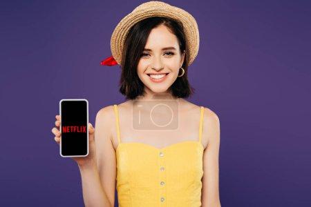 Photo pour KYIV, UKRAINE - 3 JUILLET 2019 : fille souriante en chapeau de paille tenant smartphone avec application netflix isolée sur violet - image libre de droit