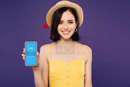 Photo pour KYIV, UKRAINE - 3 JUILLET 2019 : fille souriante en chapeau de paille tenant smartphone avec application skype isolé sur violet - image libre de droit