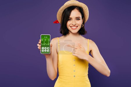 smiling girl in straw hat pointing with finger at smartphone with healthcare app isolated on purple