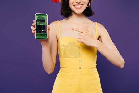 Photo pour Vue recadrée de la fille en chapeau de paille pointant du doigt le smartphone avec application de réservation isolé sur violet - image libre de droit