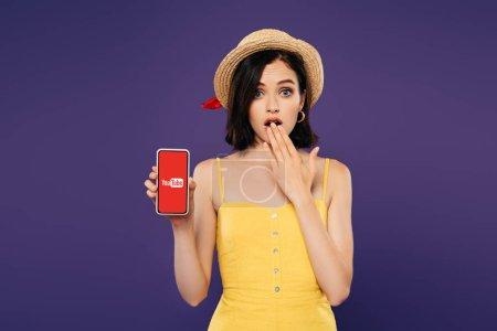 Photo pour Kiev, Ukraine - 3 juillet 2019: fille dans le chapeau de paille montrant le geste d'idée et tenant le smartphone avec le logo de youtube d'isolement sur le pourpre - image libre de droit