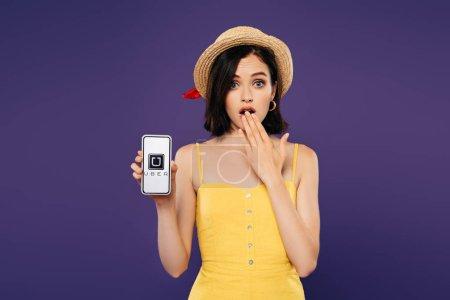 Photo pour KYIV, UKRAINE - 3 JUILLET 2019 : fille en chapeau de paille montrant geste idée et tenant smartphone avec logo uber isolé sur violet - image libre de droit