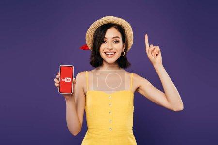 Photo pour Kiev, Ukraine - 3 juillet 2019: fille excitée dans le chapeau de paille montrant le geste d'idée et tenant le smartphone avec l'application de youtube d'isolement sur le pourpre - image libre de droit