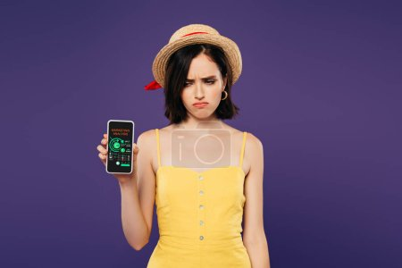 Photo for Sad pretty girl in straw hat holding smartphone with marketing analysis app isolated on purple - Royalty Free Image