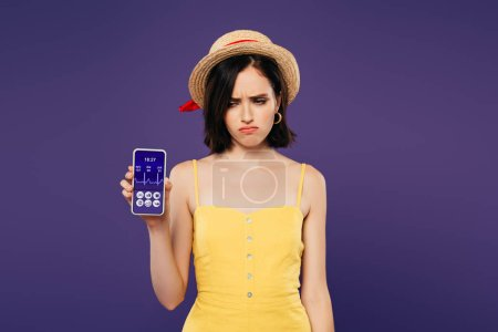 Photo for Sad pretty girl in straw hat holding smartphone with healthcare app isolated on purple - Royalty Free Image