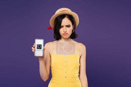 Photo pour KYIV, UKRAINE - 3 JUILLET 2019 : triste jolie fille en chapeau de paille tenant smartphone avec application uber isolé sur violet - image libre de droit