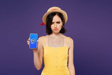 Photo pour KYIV, UKRAINE - 3 JUILLET 2019 : triste jolie fille en chapeau de paille tenant smartphone avec application shazam isolé sur violet - image libre de droit