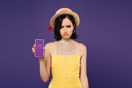 Photo for KYIV, UKRAINE - JULY 3, 2019: sad pretty girl in straw hat holding smartphone with instagram app isolated on purple - Royalty Free Image