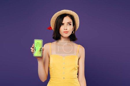 Photo pour Jolie fille rêveuse dans le smartphone de fixation de chapeau de paille avec la meilleure application d'achats d'isolement sur le pourpre - image libre de droit