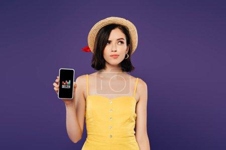 Photo pour KYIV, UKRAINE - 3 JUILLET 2019 : jolie fille rêveuse en chapeau de paille tenant smartphone avec application deezer isolé sur violet - image libre de droit