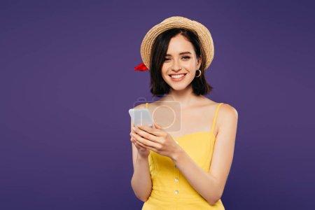 Photo pour Souriant jolie fille dans le chapeau de paille utilisant le smartphone d'isolement sur le pourpre - image libre de droit