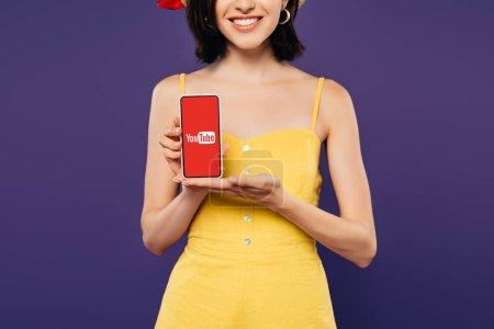 recortado vista de niña sonriente sosteniendo teléfono inteligente con aplicación aislada en púrpura