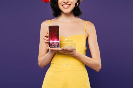 Photo for Cropped view of smiling girl holding smartphone with trading courses app isolated on purple - Royalty Free Image