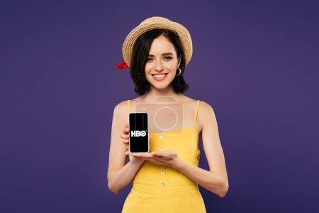 Photo pour Kiev, Ukraine - 3 juillet 2019: jolie fille souriante en chapeau de paille tenant smartphone avec l'application Hbo isolée sur le violet - image libre de droit