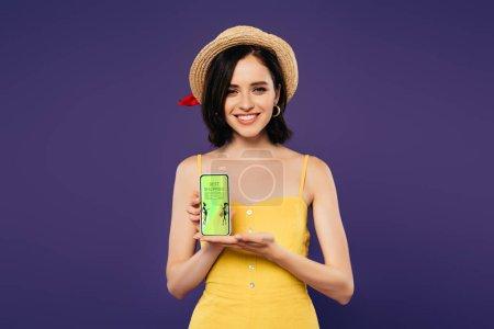 Photo pour Souriant jolie fille dans le chapeau de paille retenant le smartphone avec la meilleure application d'achats d'isolement sur le pourpre - image libre de droit
