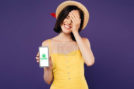 Photo pour KYIV, UKRAINE - 3 JUILLET 2019 : jolie fille souriante en chapeau de paille avec la main sur le visage montrant smartphone avec application spotify isolé sur violet - image libre de droit