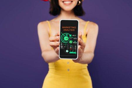 Photo pour Foyer sélectif de la fille de sourire présentant le smartphone avec l'application d'analyse de marketing d'isolement sur le pourpre - image libre de droit