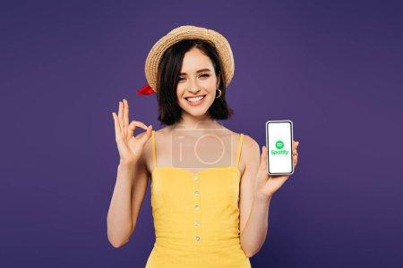 Photo pour KYIV, UKRAINE - 3 JUILLET 2019 : jolie fille souriante en chapeau de paille tenant smartphone avec application spotify et montrant ok signe isolé sur violet - image libre de droit