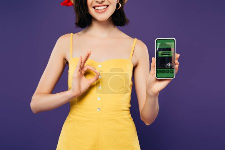 Photo for Cropped view of smiling girl in holding smartphone with booking app and showing ok sign isolated on purple - Royalty Free Image