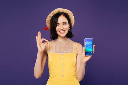 Photo pour Souriant jolie fille dans le chapeau de paille retenant le smartphone avec l'application de réservation et affichant le signe ok d'isolement sur pourpre - image libre de droit