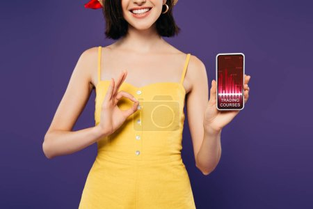 Photo for Cropped view of smiling girl in holding smartphone with trading courses app and showing ok sign isolated on purple - Royalty Free Image