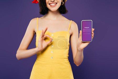 Photo pour Kiev, Ukraine - 3 juillet 2019: vue recadrée de la fille souriante dans la tenue smartphone avec l'application Instagram et montrant signe ok isolé sur le violet - image libre de droit