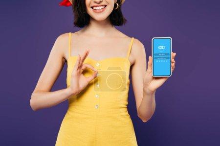 Photo pour Kiev, Ukraine - 3 juillet 2019: vue recadrée de la fille souriante dans la tenue du smartphone avec le logo skype et montrant signe ok isolé sur le violet - image libre de droit