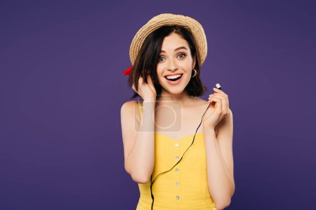 Photo for Excited smiling pretty girl in straw hat putting on earphones isolated on purple - Royalty Free Image