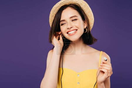 Photo for Smiling pretty girl in straw hat with closed eyes putting on earphones isolated on purple - Royalty Free Image
