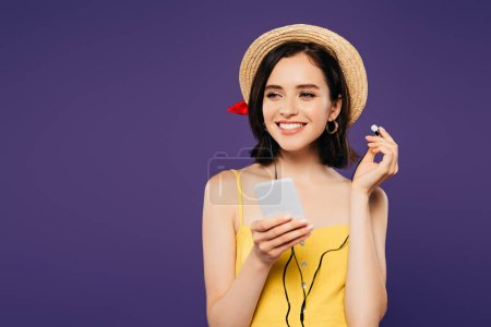 Photo pour Souriant jolie fille dans la musique d'écoute de chapeau de paille dans des écouteurs sur le smartphone et regardant loin isolé sur le pourpre - image libre de droit
