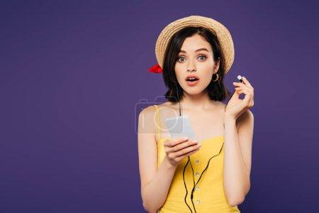 Photo pour Choqué jolie fille dans la musique chapeau de paille écoute dans les écouteurs sur smartphone isolé sur violet - image libre de droit
