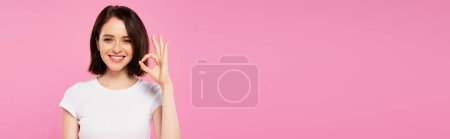 Photo for Panoramic shot of smiling pretty girl showing okay sign isolated on pink - Royalty Free Image
