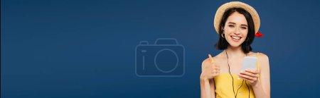 Photo pour Plan panoramique de jolie fille souriante en chapeau de paille écoutant de la musique dans les écouteurs sur smartphone et montrant pouce vers le haut isolé sur bleu - image libre de droit