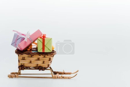 Photo for Small and toy sleigh with colorful gifts isolated on white - Royalty Free Image