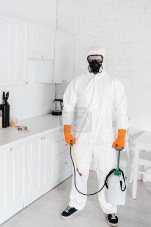 exterminator in protective mask and uniform holding toxic equipment while standing near kitchen cabinet