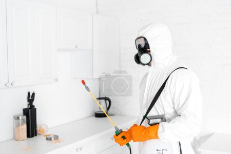 exterminator in protective mask holding toxic equipment near kitchen cabinet