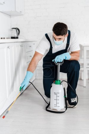 exterminator in protective mask holding toxic spray near kitchen cabinet