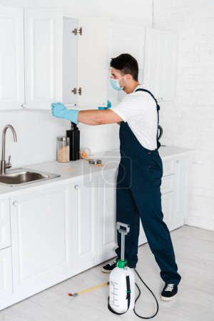 exterminator standing near kitchen cabinet and toxic equipment on floor