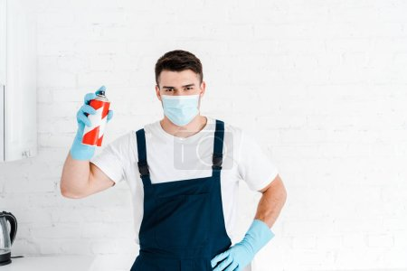 Photo for Exterminator in latex gloves holding toxic spray can and standing with hand on hip - Royalty Free Image