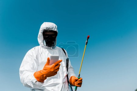 exterminator using smartphone while holding spray against sky