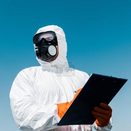 Photo pour Exterminateur dans un masque de protection tenant presse-papiers - image libre de droit