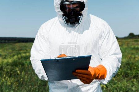 Photo pour Homme en masque de protection et écriture uniforme tout en tenant presse-papiers - image libre de droit