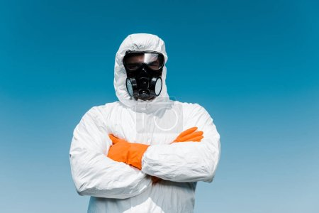 Photo pour Exterminateur en masque de protection et debout uniforme avec bras croisés - image libre de droit